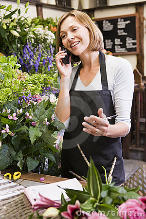 Woman working at flower shop using telephone