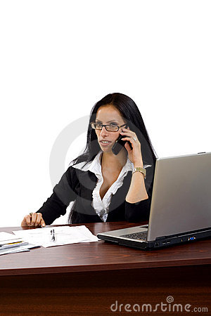 Woman working with laptop holding phone