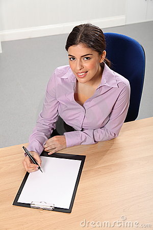 Woman working in office looks up while writing