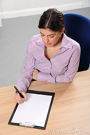Woman working in office writing at her desk