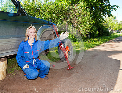 The woman in working overalls tries to replace a wheel at an off-road car, and asks the help