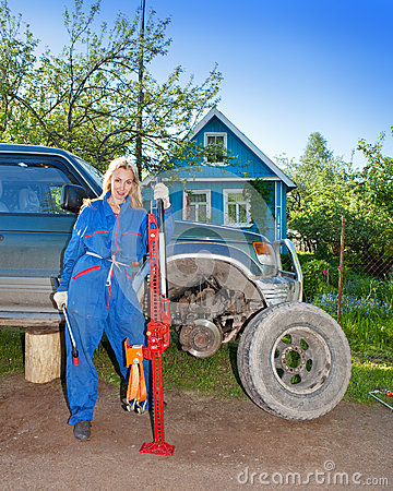 The woman in working overalls tries to replace a wheel at an off-road car