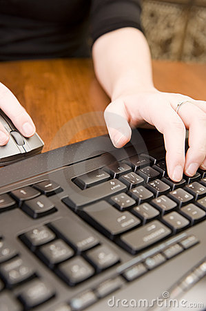 Woman working on PC keyboard and mouse.