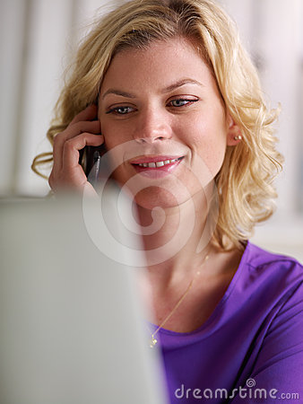 Woman working with pc and speaking on the phone