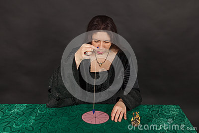 A woman is working with a pendulum