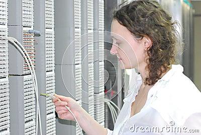 Woman working on telecommunication equipment