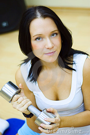 Woman works with dumbbell.