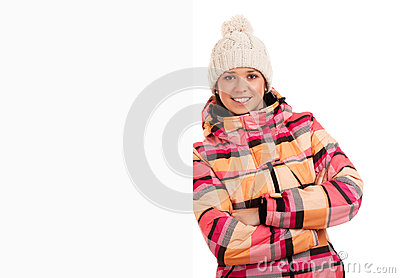 Woman in worm cloth standing by blank board