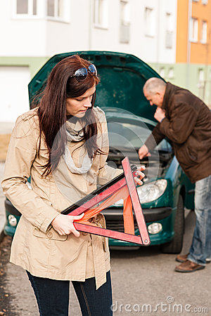 Woman worried about broken car warning sign
