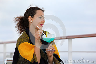 Woman wrapped in blanket sits on cruise liner deck
