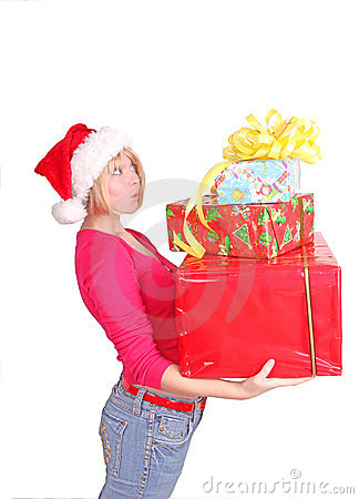 Woman wrapping christmas presents wearing santa ha