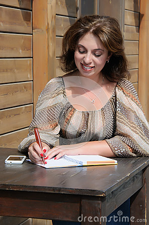 Woman writing something to the notebook using pen