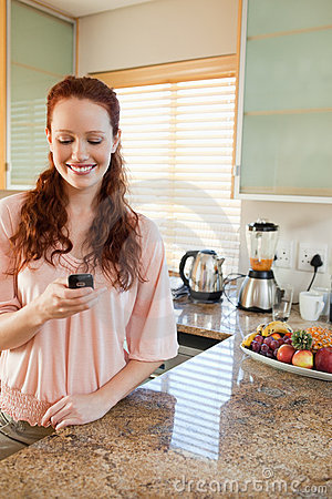 Woman writing text message in the kitchen