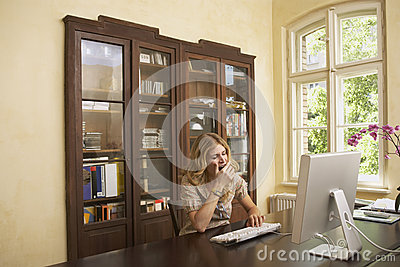 Woman Yawning Over Computer In Study Room