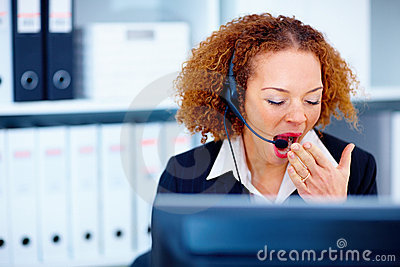 Woman yawning while using headset in office