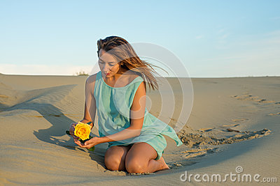Woman with a yellow rose sits on the sand