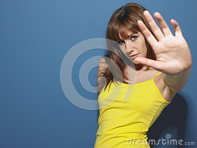 Woman In Yellow Tank Top Gesturing Stop Sign