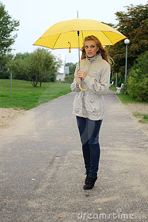 Woman with yellow umbrella in the park