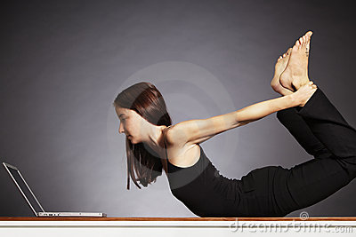 Woman in yoga bow pose with laptop.