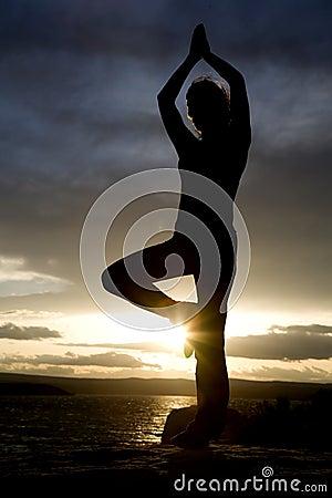 Woman yoga one leg up sun flare