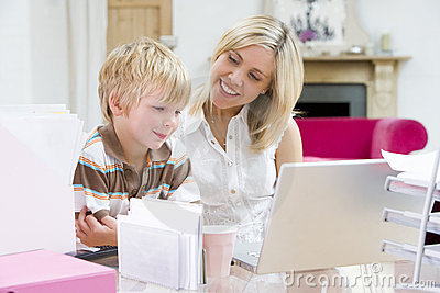 Woman and young boy in home office with laptop