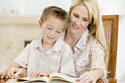 Woman and young boy reading book in dining room