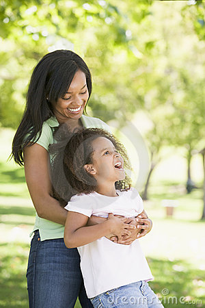 Woman and young girl  embracing and smiling
