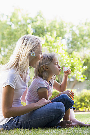 Woman and young girl outdoors blowing bubbles
