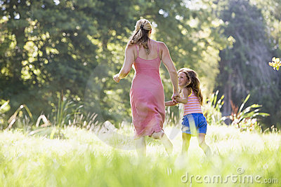 Woman and young girl running holding hands