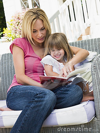 Woman and young girl sitting on patio reading book