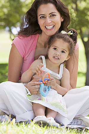 Woman and young girl sitting with toy smiling