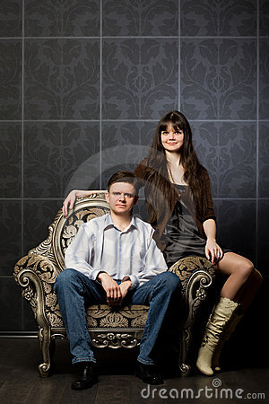 Woman and young man sitting in ancient armchair
