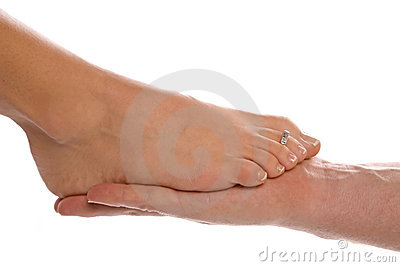 Womans foot on mans hand