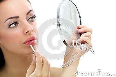 Women apply lipstick in front of mirror