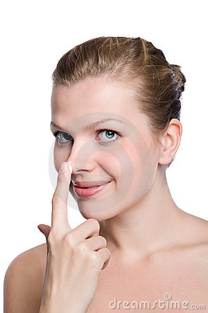 Women applying cream to her nose