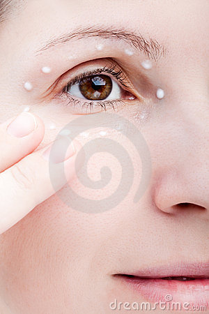Women applying eye skin cream