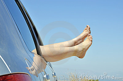 Women with bare feet out the window of the car