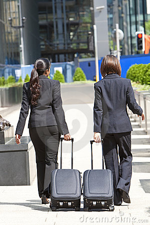 Women Business Travellers With Rolling Suitcases