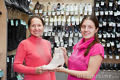 Women chooses shoes at shoes shop