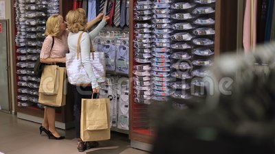 Women choosing necktie during apparel shopping stock footage