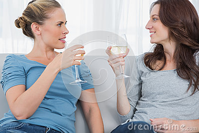 Women clinking their wine glasses while sitting on the sofa