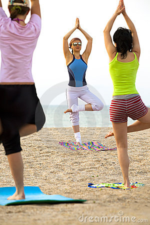 Women doing fitness exercise on a beach