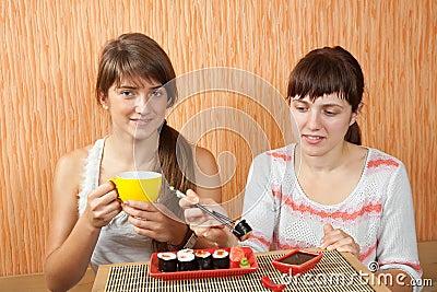Women eating sushi rolls