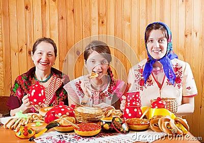 Women eats pancake  during  Shrovetide