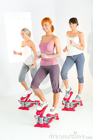 Women exercising on stepping machine