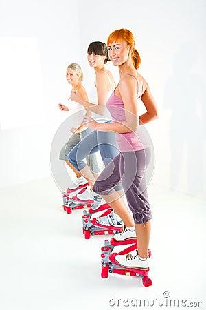 Women exercising on stepping machine
