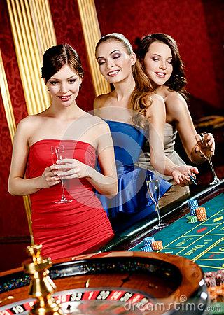 Women with glasses of spirits play roulette