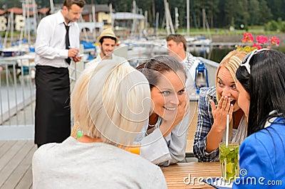 Gossiping women sitting at harbor bar