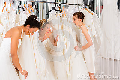 Women having fun during bridal dress fitting in shop