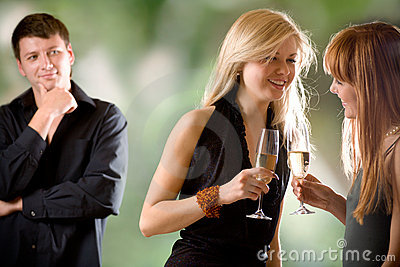 Women holding glasses with champagne and laughing and young man